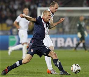 United States' Jay DeMerit (blue) vies with England's Wayne Rooney for the ball in Saturday's match.