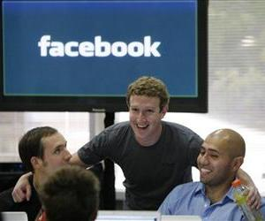 Facebook CEO Mark Zuckerberg, center, smiles with unidentified co-workers at Facebook headquarters in Palo Alto, Calif., Wednesday, Oct. 5, 2010.