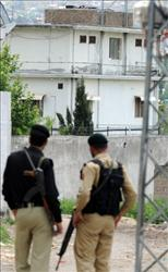A Pakistani soldier and policeman stand in a cordoned-off street as they look at the final hideout of Osama bin Laden.
